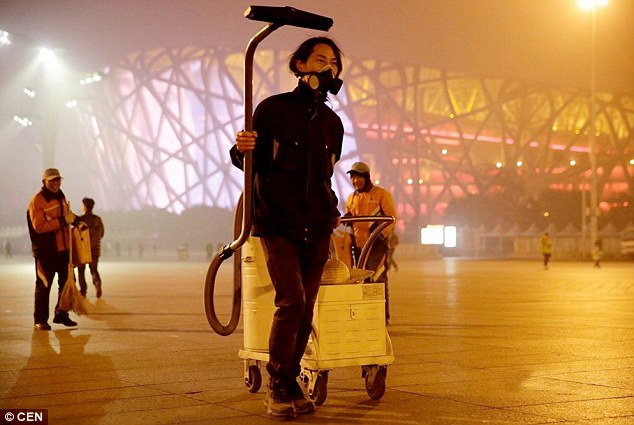 Walking around Beijing with an industrial vacuum, artist Brother Nut also wears a face mask to protect himself